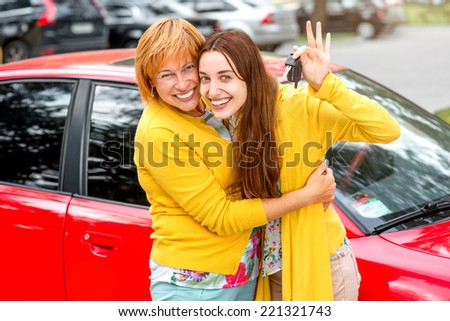 Mother with her daughter near red car - stock photo