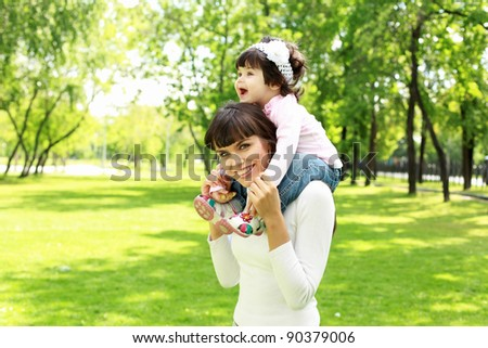 Mother with her daughter outside in the summer park - stock photo