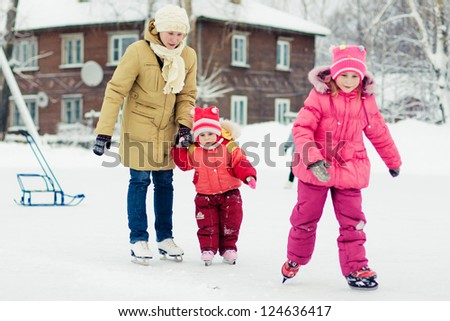 Mother with her daughters skates on ice skating in the winter. - stock photo