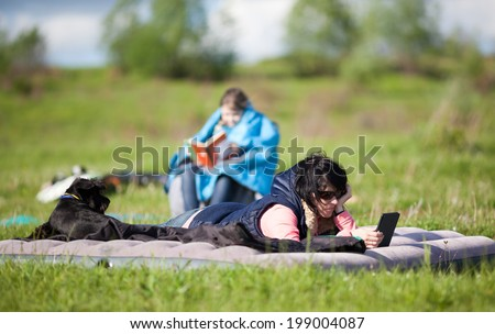 Mother with her dog lying on the inflatable mattress and reading a ebook. Daughter with book on background - stock photo