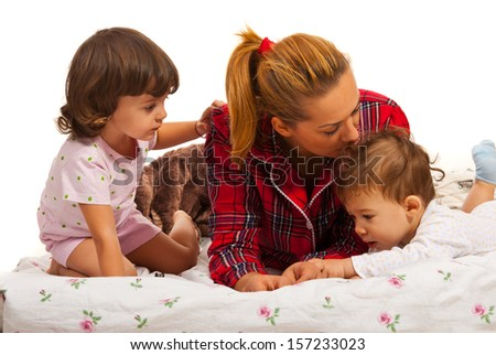 Mother with her kids lying on bed and mom kissing little baby head - stock photo