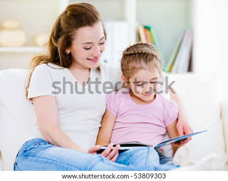 Mother with her little pretty daughter reading a book at home - stock photo