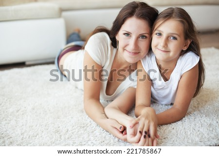 Mother with her preteen daughter having fun on a white carpet in living room at home - stock photo