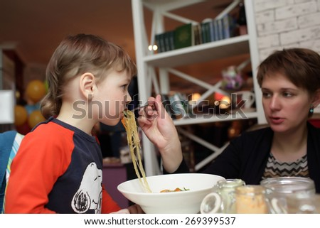 Mother with her son have noodles in the restaurant - stock photo