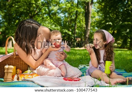 Mother with her two children having picnic in park - showing apple to baby - stock photo