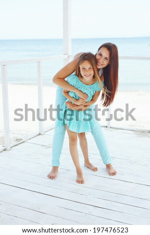 Mother with her 7 years old daughter having fun at beach in summer - stock photo
