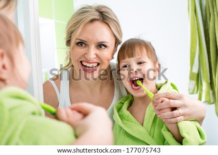 mother with kid brushing teeth - stock photo