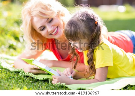 Mother with kid daughter lying in summer park - stock photo