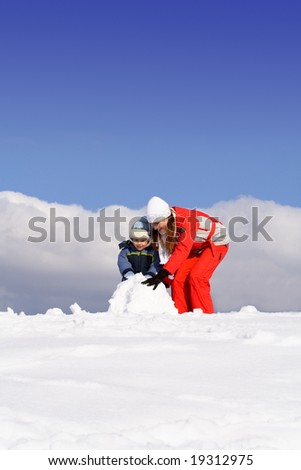 Mother with kid making snowman in winter park - stock photo