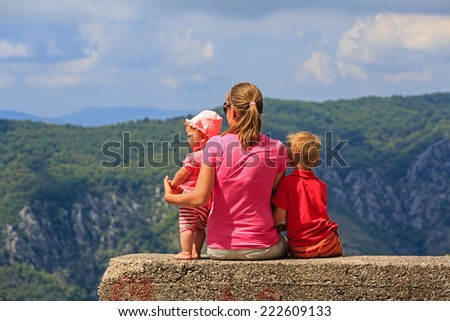 mother with kids having rest on vacation in mountains - stock photo