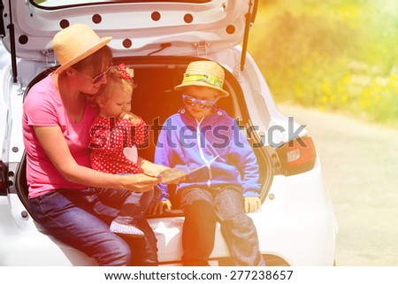 mother with kids looking at map while travel by car - stock photo