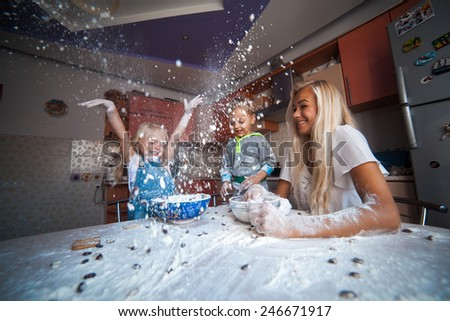 Mother with kids on kitchen play with flower - stock photo