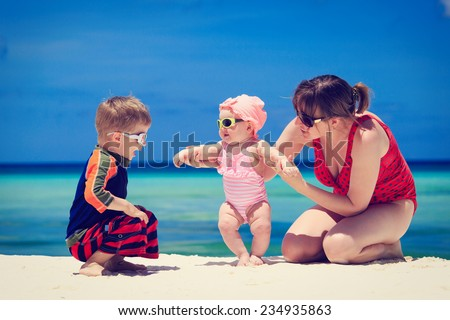 mother with kids playing on tropical sand beach - stock photo