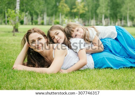 Mother with kids spending free time playing outdoors. Family has the same clothes. Children lie on mom's back  - stock photo