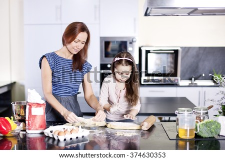 Mother with little daughter cooking in the kitchen at home. Girl Assisting In Preparing Food - Stock image  - stock photo