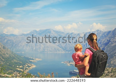 mother with little daughter looking at mountains on vacation - stock photo