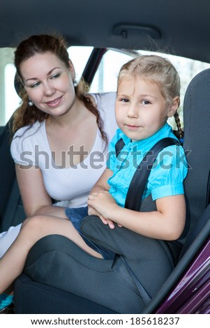 Mother with little daughter sitting on back seat of car - stock photo