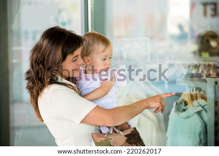 Mother with little girl in white dress looking through shop window - stock photo