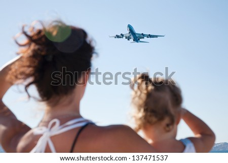 Mother with little girl looking at the plane flying in the sky - stock photo