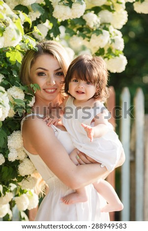 Mother with long blonde hair and flower wreath on had holding and playing with her baby girl in summer green park outdoor. Smiling mother and little daughter on nature. Happy people outdoors - stock photo