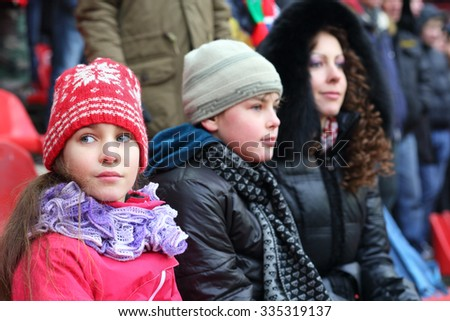 Mother with son and daughter in warm clothing sitting on stadium, focus on girl - stock photo