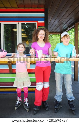 Mother with son and daughter on the rollers in a summer cafe in park - stock photo