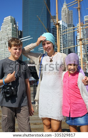 Mother with son and daughter standing on the pier near the sailing ship in New York - stock photo