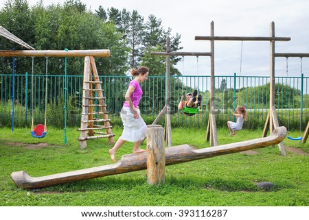Mother with son and daughter swinging on a swing on a wooden playground - stock photo