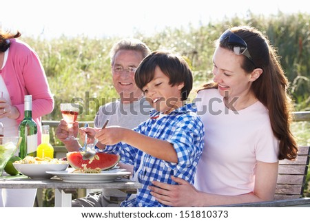 Mother With Son And Grandfather Enjoying Outdoor Barbeque - stock photo