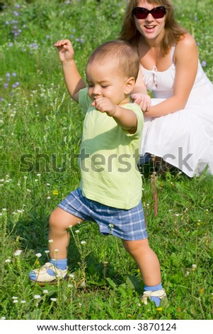 Mother with son playing in grass - stock photo