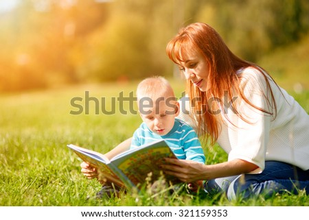 Mother with son reading book in park - stock photo
