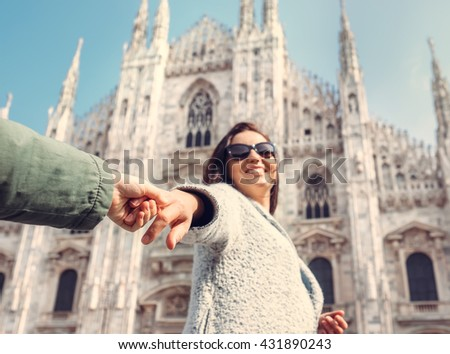 Mother with son take with hands and run together to Duomo di Milano - stock photo
