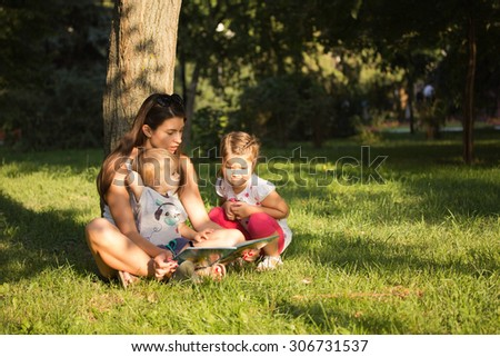 Mother with the children in the park reading a book - stock photo
