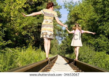 Mother with the daughter go on rails, a back to a camera, in a wood, in the summer, wood - stock photo