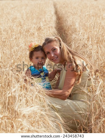 Mother with the little daughter in the field of ripe wheat - stock photo