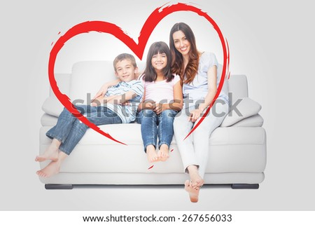 Mother with their children sitting on sofa against heart - stock photo
