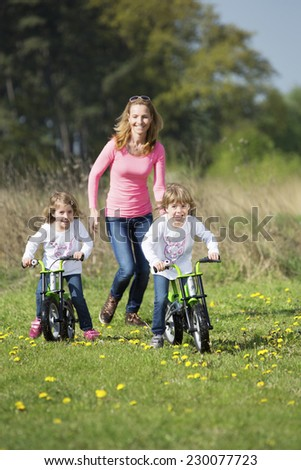 Mother with twin girls, riding bikes - stock photo