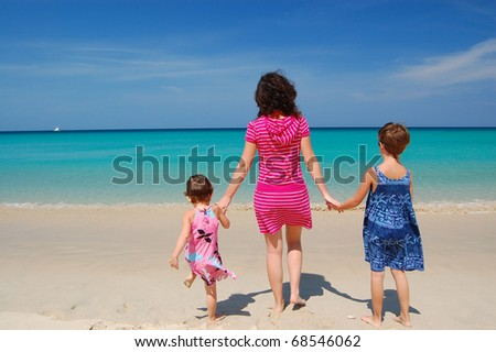 Mother with two daughters on the beautiful tropical beach - stock photo