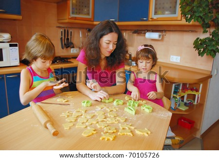 Mother with two kids baking together - stock photo