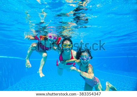 mother with two little girls played under water in the pool - stock photo