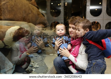 Mother with two sons in a museum - stock photo