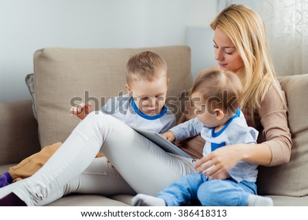 Mother with two sons looking photo on digital tablet at home - stock photo
