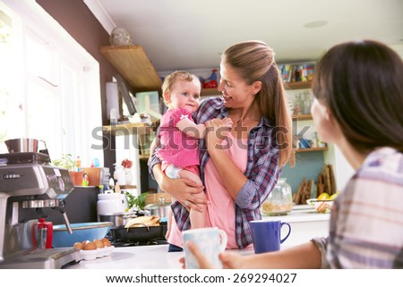 Mother With Young Daughter Talking To Friend In Kitchen - stock photo