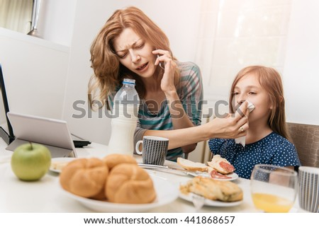 Mother working at home in the kitchen with daughter - stock photo
