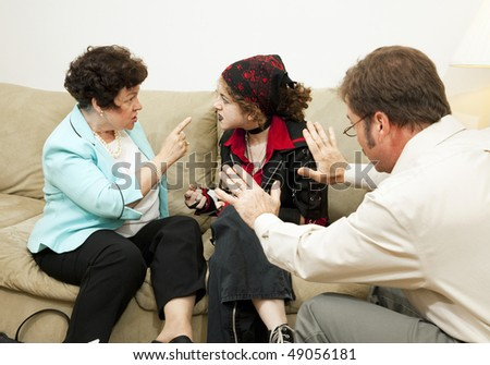 Mother yelling at her teen daughter during a family counseling session. - stock photo
