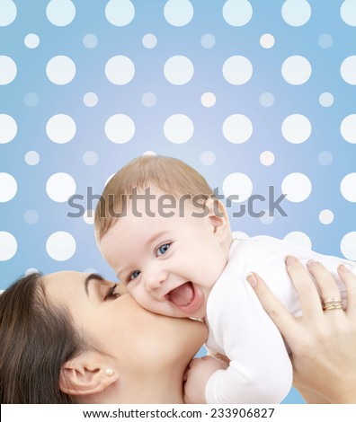 motherhood, children, adoption, happiness and people concept - happy mother kissing her baby boy over blue and white polka dots pattern background - stock photo