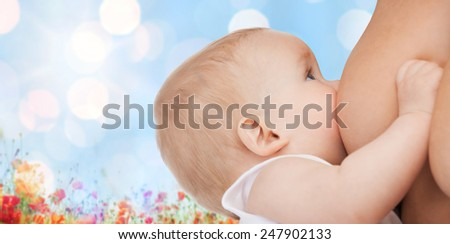 motherhood, children, people and care concept - close up of mother breast feeding adorable baby over blue sky with lights and poppy field background - stock photo