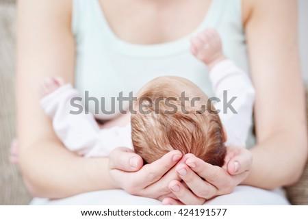 Motherhood. newborn baby on mother hands - stock photo