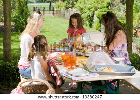 Mothers and their daughters having a picnic outdoors on a summer day - stock photo