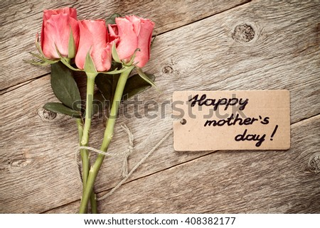 Mothers day card with roses on wooden board. - stock photo